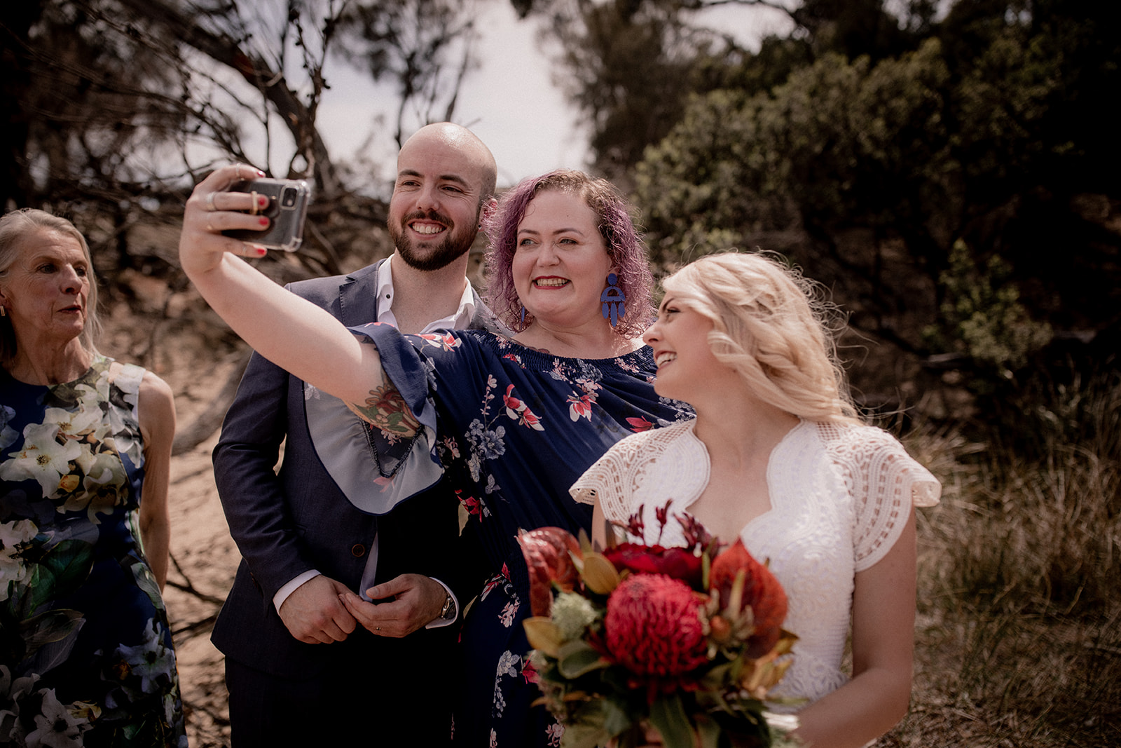 a professional photo of a selfie, the purple-haired celebrant stands in between the bride and groom and they are all grinning at the phone camera
