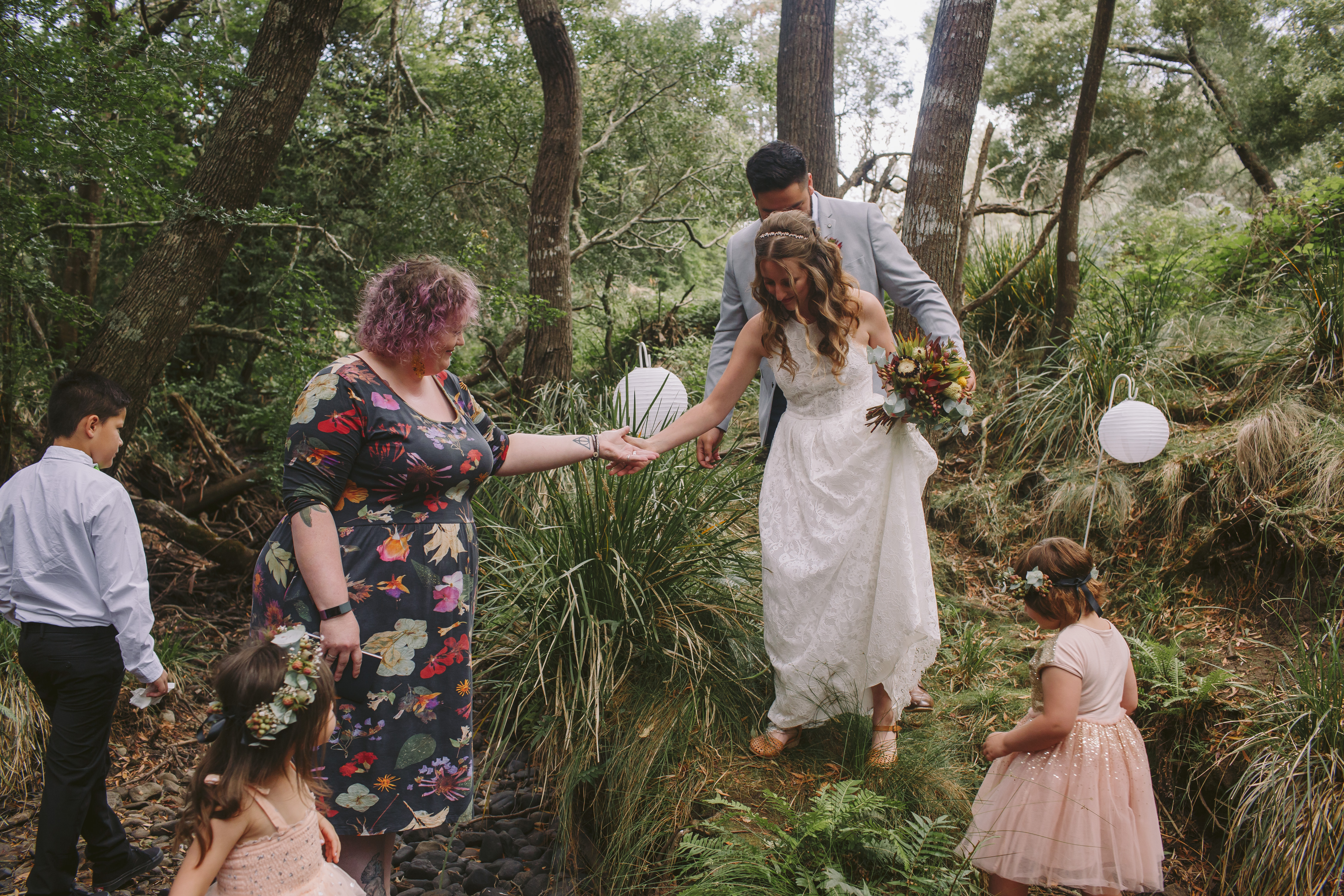 a person with curly purple hair in a botanical print dress holds their hand out to help a bride about to take a step down into the creekbed, her groom is behind her and they are surrounded by the bush