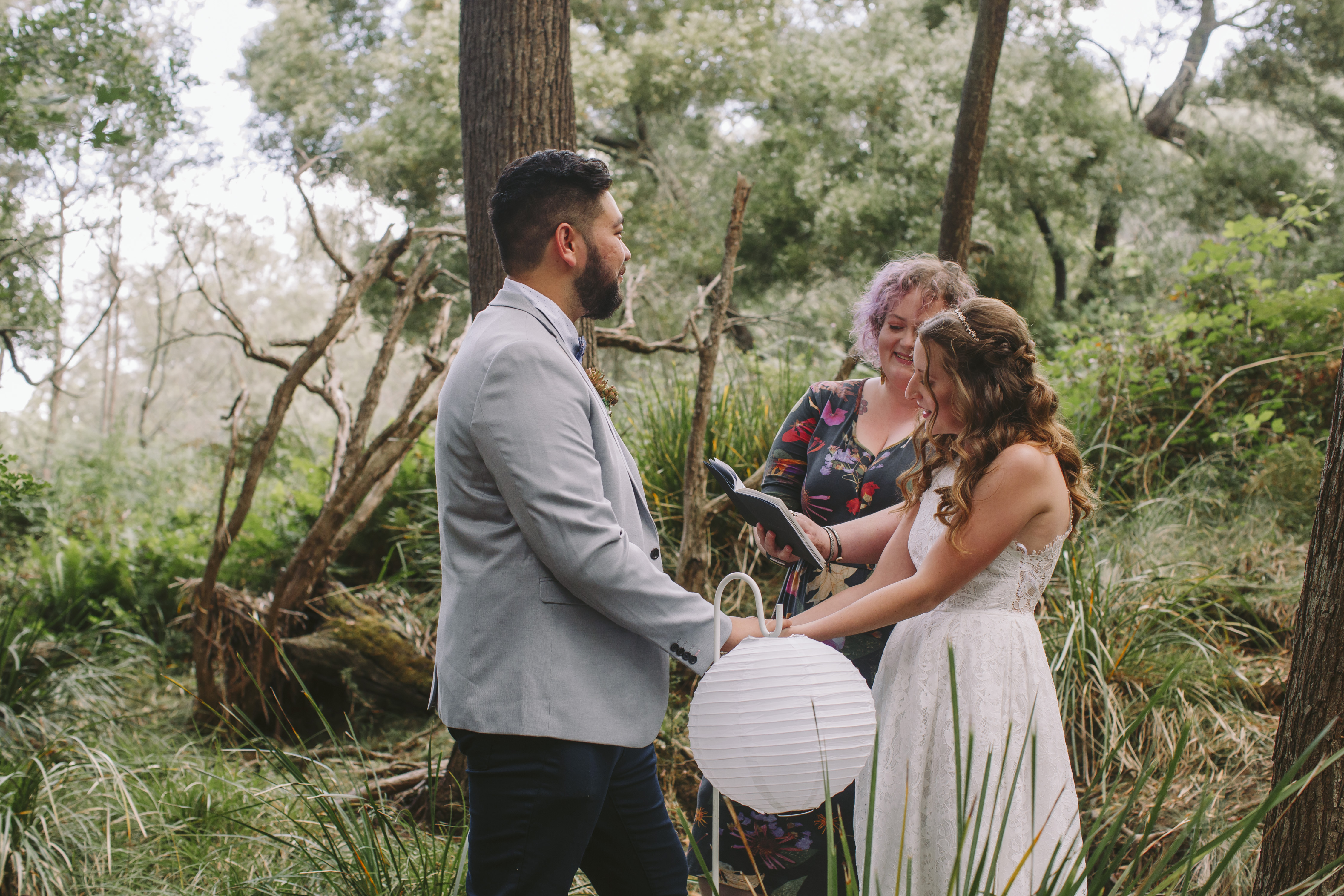 two people are getting married, holding hands in a bush setting, and a third person is leaning in with their vows for them to read