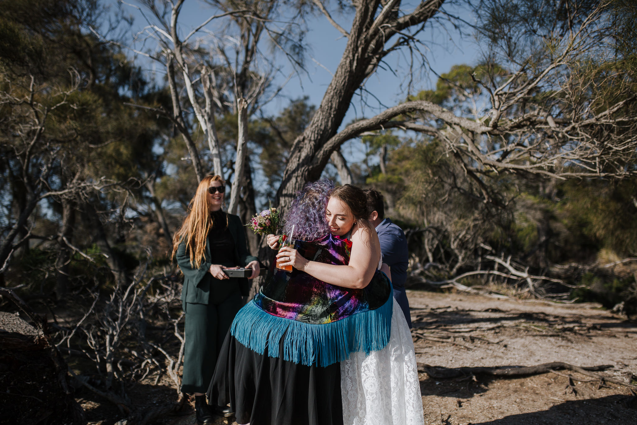 two people hug in the foreground, one is wearing a rainbow cape with bright blue tassels and the other is wearing a white dress and holding a celebratory drink, two others people are waiting close by, they are all in a national park and surrounded by gnarly tree branches