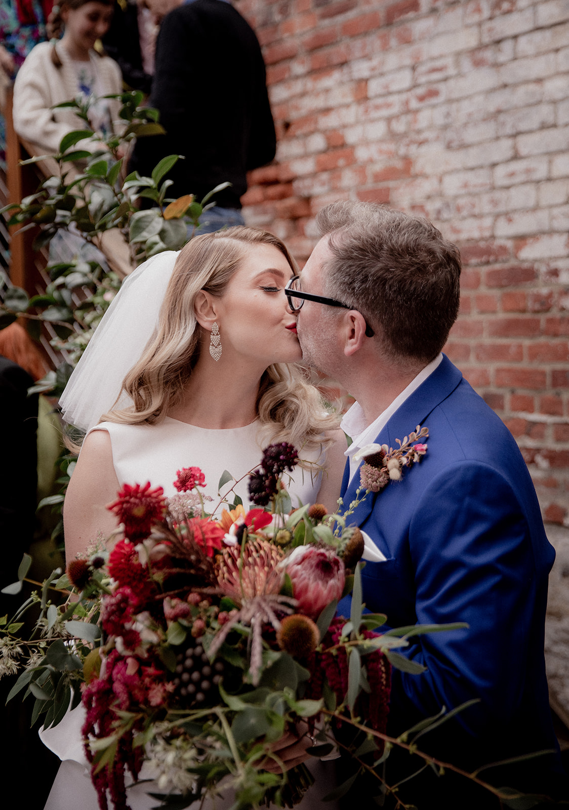 a just-married couple kiss over their bouquet of autumnal colours