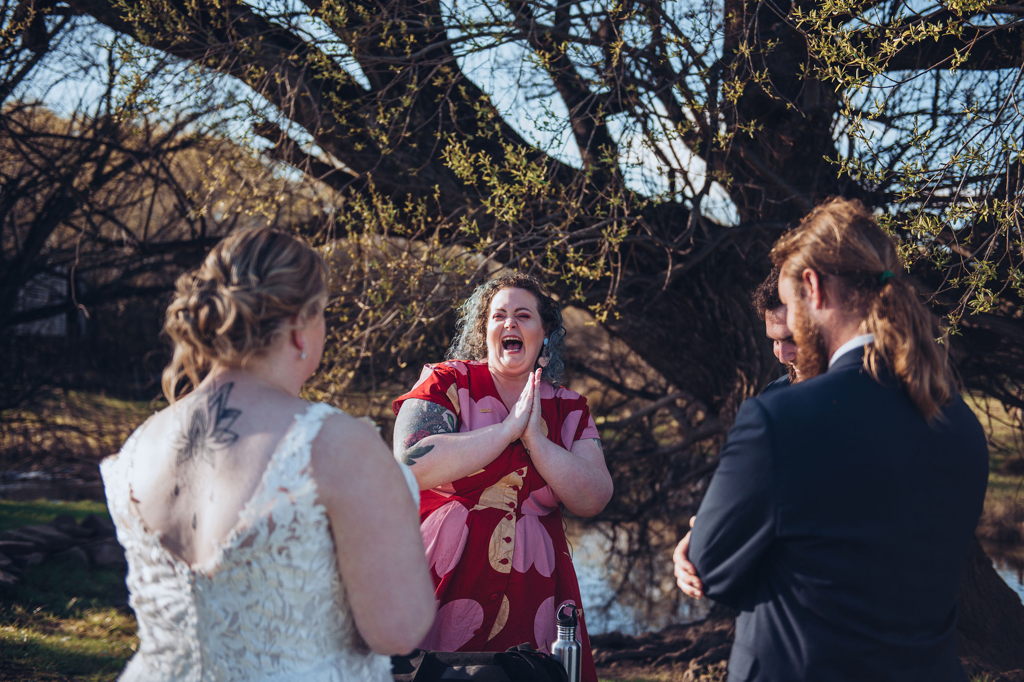 a candid moment caught on camera of the colourful celebrant cackling with glee post-ceremony at the signing table, hands clasped together