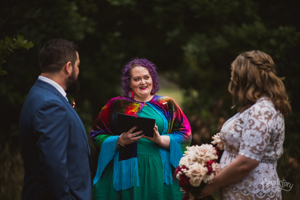 a person with curly purple hair in a bright green dress and a magical purple cape holds an iPad and stands between a bride in a white lace dress and groom in a dark blue suit as they face her, she is in the process of marrying them