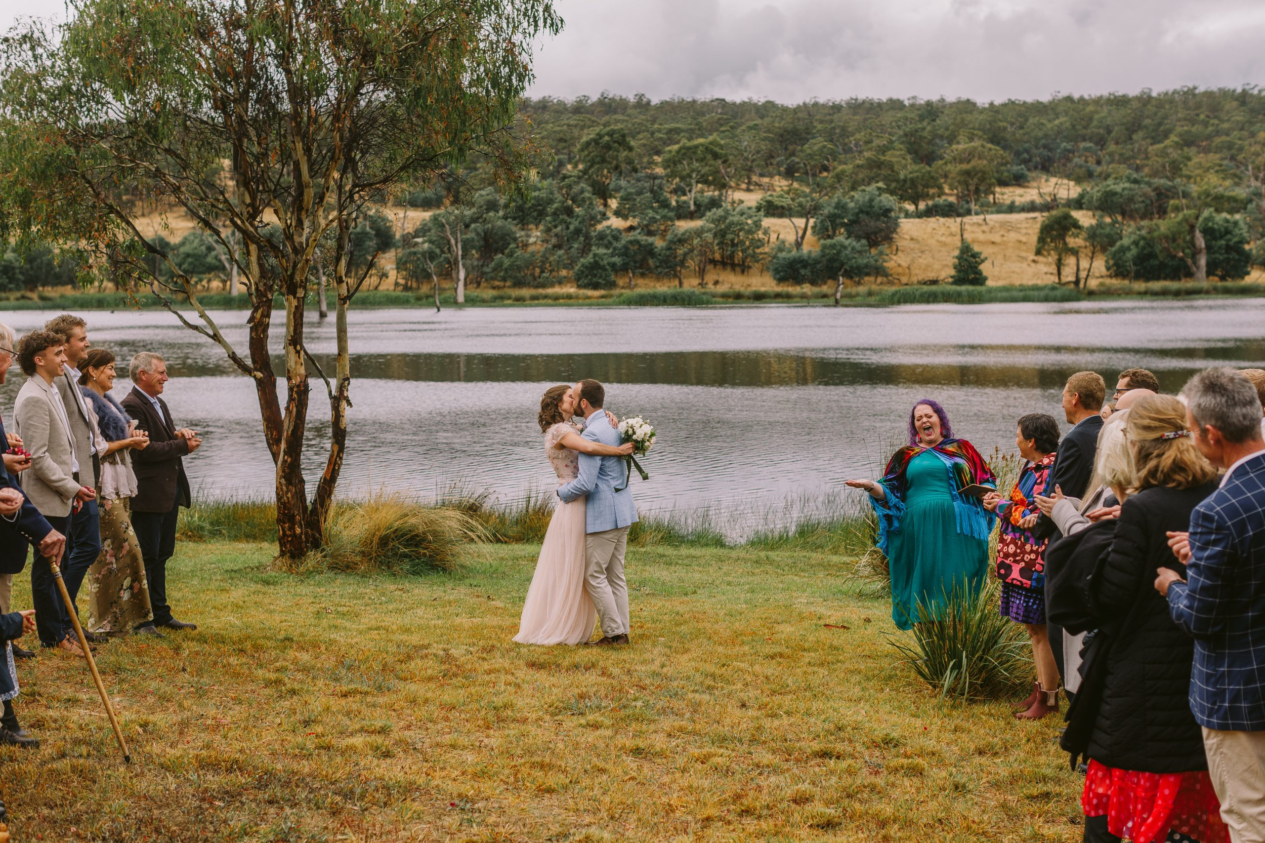 a newlywed couple kiss in front of a lake while their guests stand in two rows either side of them, looking on (and ready to throw flower petals as they walk back up between the rows). A brightly coloured celebrant with purple hair stands to the side making an overenthusiastic face as she declares them newly married!
